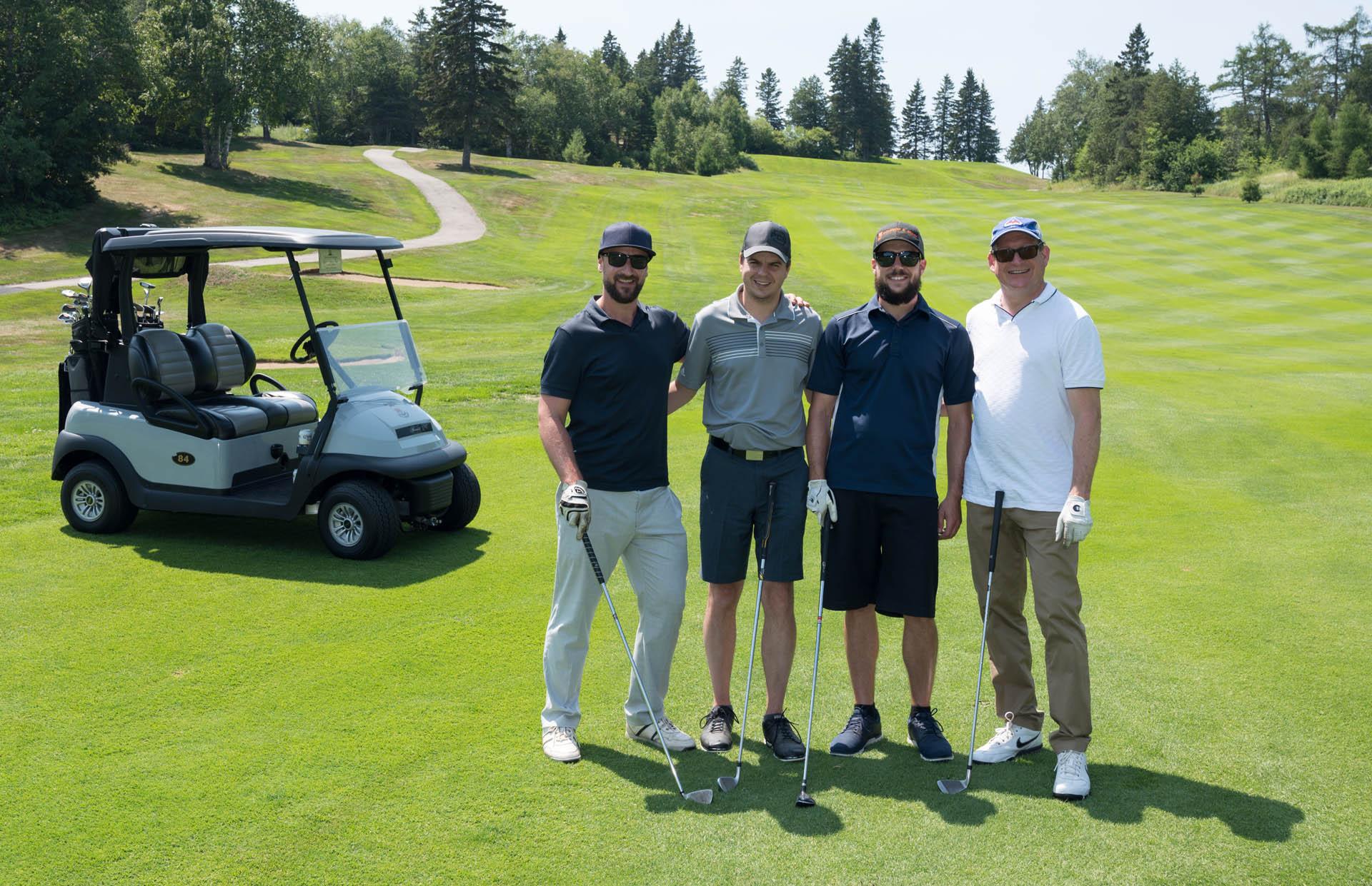 quatre joueurs de golf devant un cart